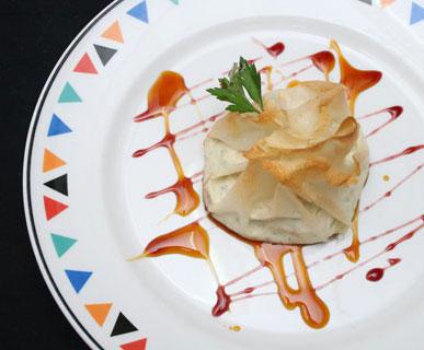 Bolsita crujiente rellena de crema de queso de Uga y mariscos con reducción de tinto y Guarapo
